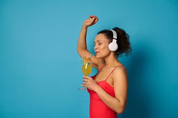 Retrato do lado de uma mulher em um maiô vermelho bebendo suco de um canudo e curtindo ouvir música com fones de ouvido.