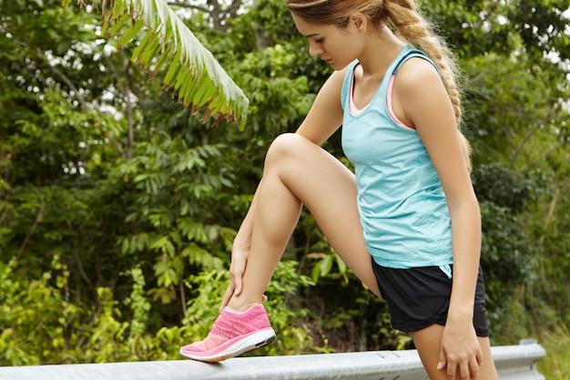 Retrato do lado do corredor de mulher loira bonita com longa trança no sportswear relaxante após a maratona, massageando seu tornozelo.