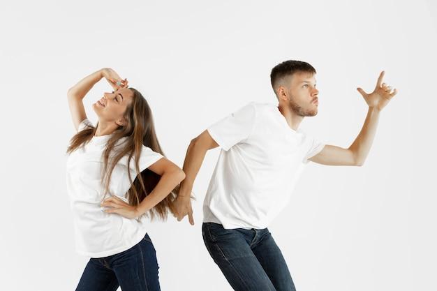 Retrato do lindo casal jovem isolado no fundo branco do estúdio. expressão facial, emoções humanas, conceito de publicidade. copyspace. mulher e homem dançando e sorrindo, apontando, parece legal.