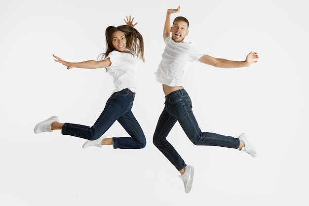 Retrato do lindo casal jovem isolado no fundo branco do estúdio. expressão facial, emoções humanas, conceito de publicidade. copyspace. mulher e homem pulando, dançando ou correndo juntos.
