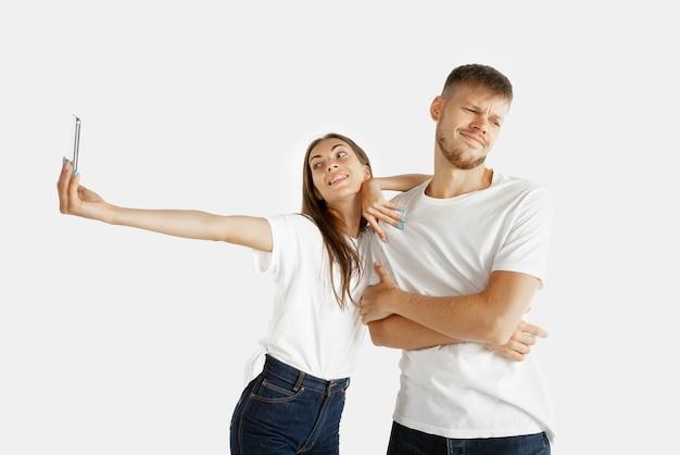Retrato do lindo casal jovem isolado no fundo branco do estúdio. expressão facial, emoções humanas, conceito de publicidade. mulher fazendo selfie ou vídeo para vlog, homem fica entediado, não quer fazer.