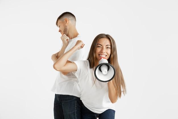 Retrato do lindo casal jovem isolado no fundo branco do estúdio. expressão facial, emoções humanas, conceito de publicidade. mulher gritando de paz na boca, louca e feliz. o homem é indiferente.
