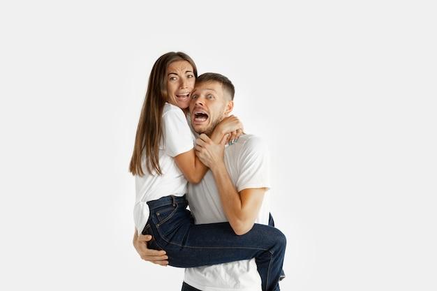 Retrato do lindo casal jovem isolado no fundo branco do estúdio. expressão facial, emoções humanas, publicidade, conceito de relação. homem e mulher abraçados, parecem assustados, gritando.