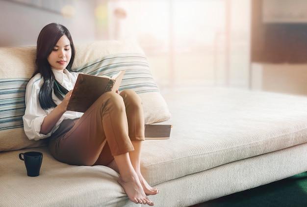 Retrato do livro de leitura asiático novo da mulher na sala de visitas com luz solar na manhã.