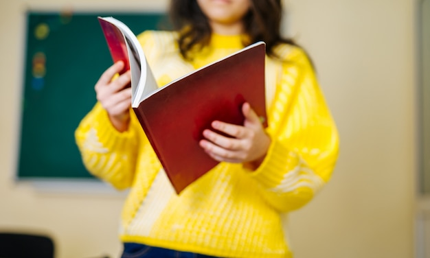 Retrato do livro de leitura bonito da menina na sala de aula