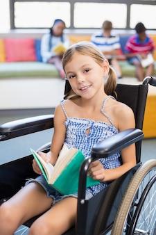 Retrato do livro de leitura da menina da escola com deficiência na biblioteca