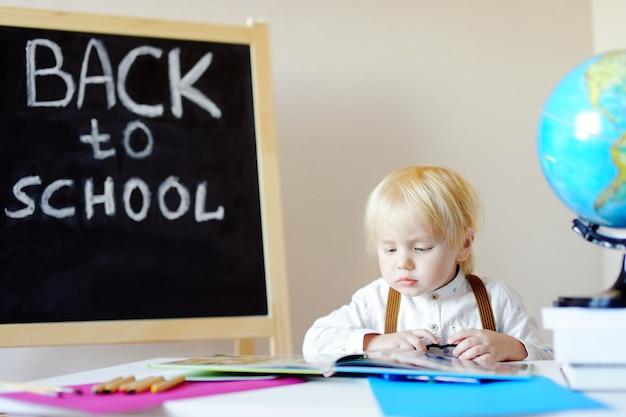 Retrato do livro de leitura do rapaz pequeno no local de trabalho.