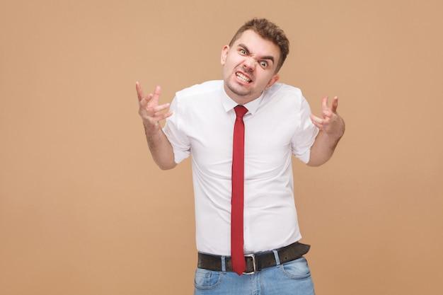 Retrato do malvado empresário de raiva. conceito de pessoas de negócios, emoções e sentimentos bons e ruins. foto de estúdio, isolada em fundo marrom claro