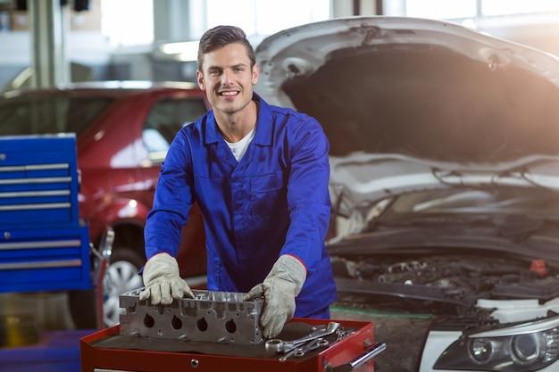 Retrato do mecânico que verific um carro peças