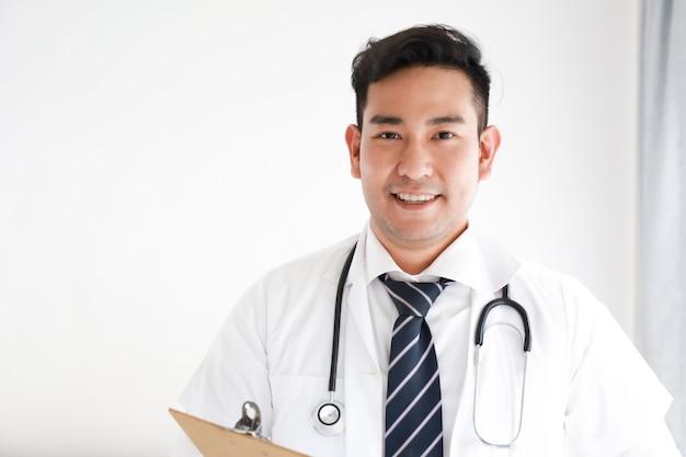 Retrato do médico asiático no hospital branco