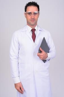 Retrato do médico bonito com óculos de proteção em branco
