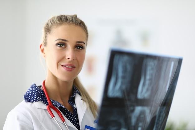 Retrato do médico com o estetoscópio nas mãos de um raio-x. diagnóstico de pneumonia e conceito de pneumonia