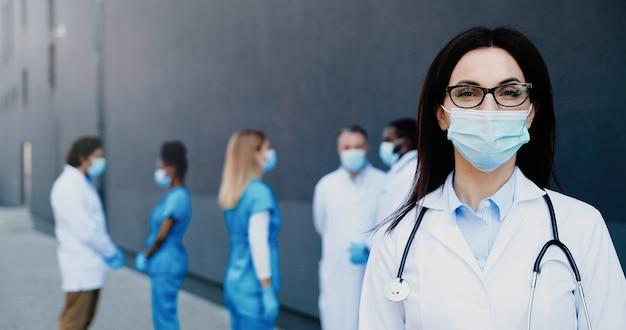 Retrato do médico da jovem morena linda mulher branca na máscara médica, olhando para a câmera. perto da médica em proteção respiratória. colegas de médicos de raças mistas no fundo.