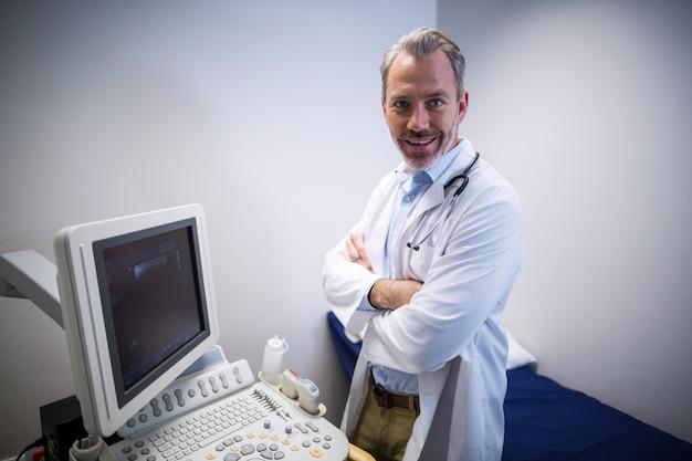 Retrato do médico em pé perto da máquina de monitoramento de pacientes na enfermaria