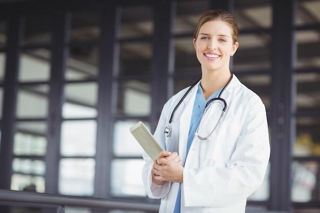 Retrato do médico feminino confiante segurando o tablet digital