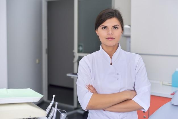 Retrato do médico feminino jovem confiante com as mãos postas