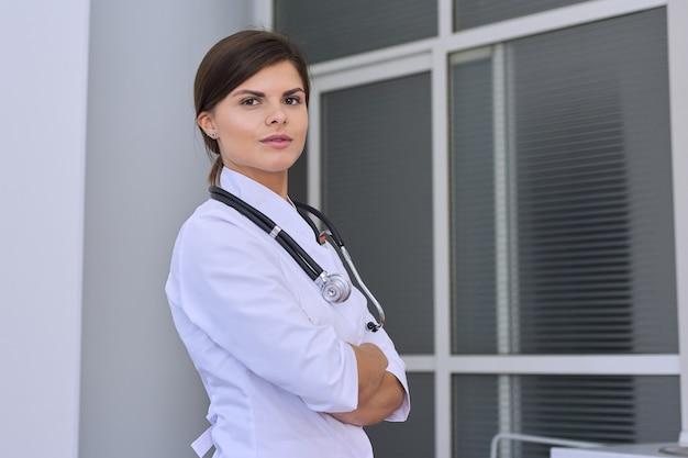 Retrato do médico feminino jovem confiante com estetoscópio com as mãos postas