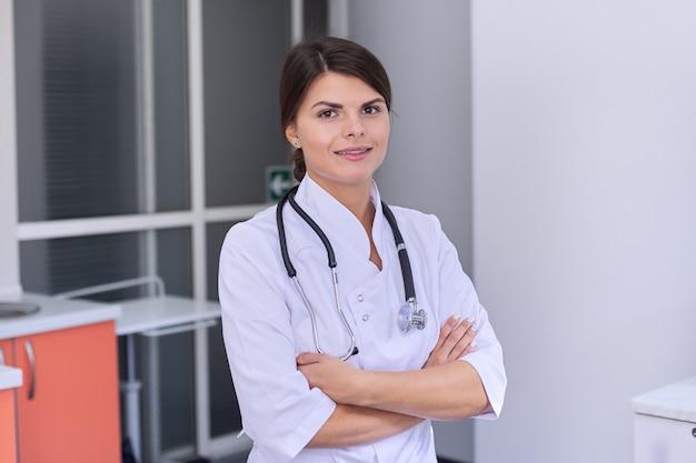 Retrato do médico feminino jovem confiante com estetoscópio com braços cruzados
