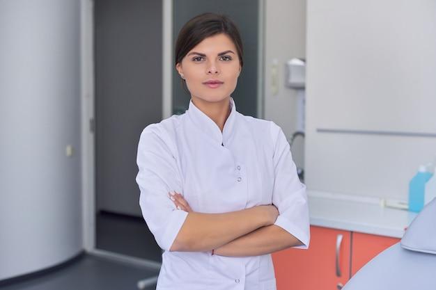 Retrato do médico feminino jovem confiante com os braços cruzados