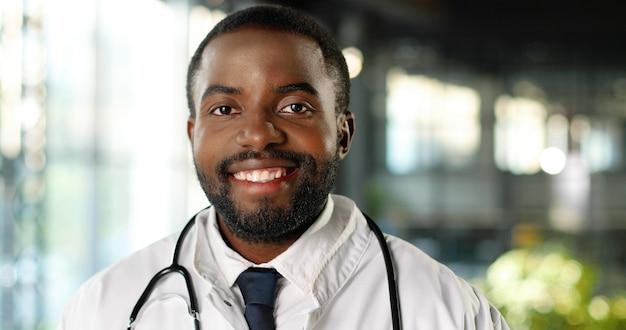 Retrato do médico jovem afro-americano com estetoscópio, sorrindo alegremente para a câmera. sorriso bonito médico masculino feliz. médico em vestido branco na clínica. interior.