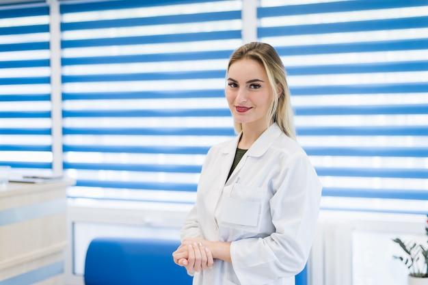 Retrato do médico jovem com pé de jaleco branco no hospital