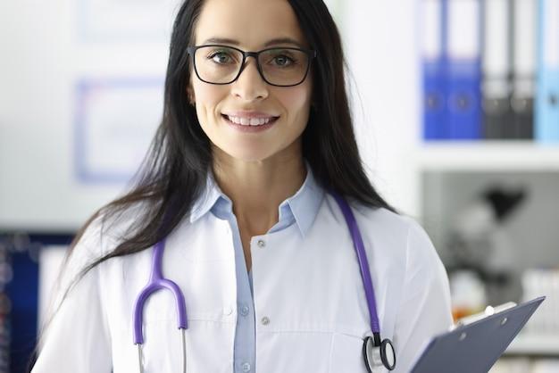 Retrato do médico sorridente com óculos no consultório médico. conceito de cuidados e serviços médicos