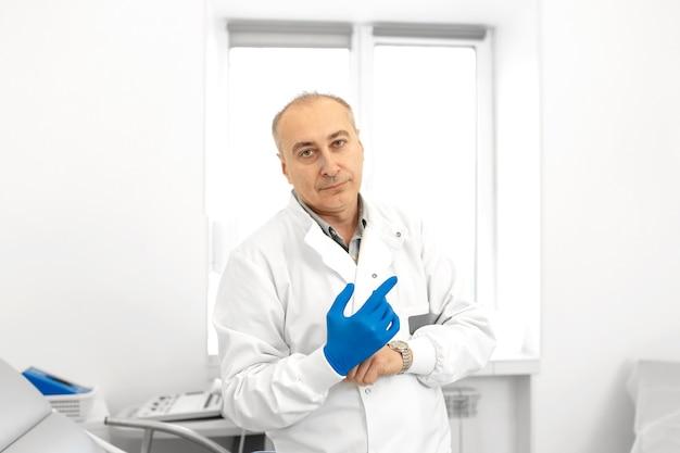 Retrato do médico urologista calçando luvas médicas antes de examinar um paciente