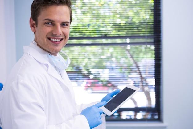 Retrato do médico usando o tablet em pé contra a parede