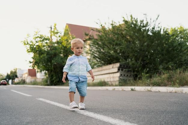 Retrato do menino bonitinho andando na estrada em seu bairro