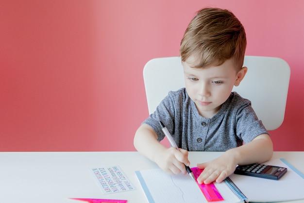 Retrato do menino bonito da criança em casa que faz trabalhos de casa. criança concentrada pequena escrevendo com lápis colorido, dentro de casa. ensino fundamental e educação.