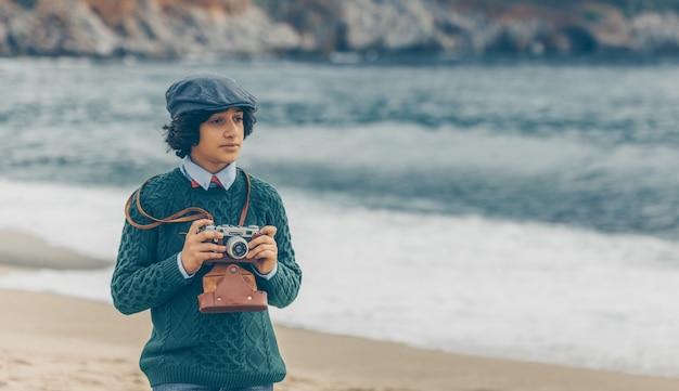 Retrato do menino que guarda a camerand do vintage que olha pensativa no litoral durante o dia.