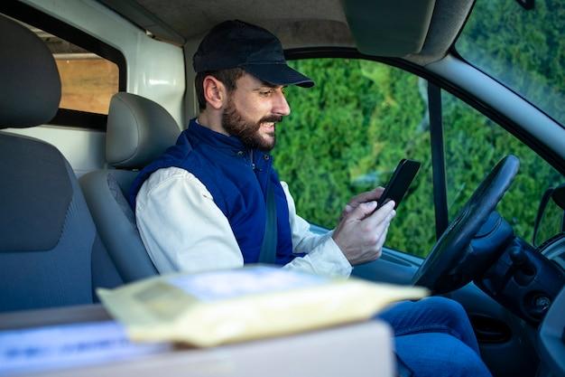Retrato do mensageiro em uma van entregando o pacote no local apropriado.