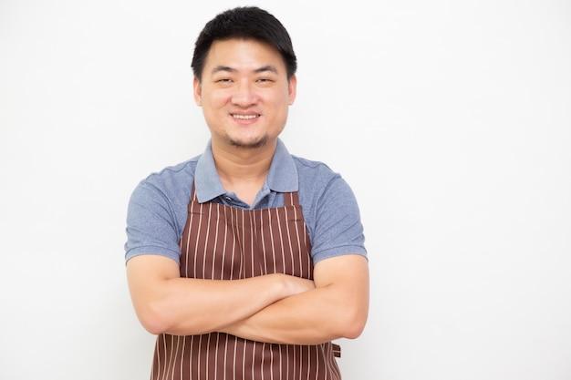 Retrato do mercado de produtos frescos asiáticos dos trabalhadores com o avental marrom que está com os braços cruzados isolados na parede branca