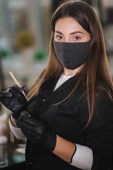 Retrato do mestre de sobrancelhas feminino profissional com manto preto com luvas pretas e máscara protetora preta usando pincel e henna para as sobrancelhas