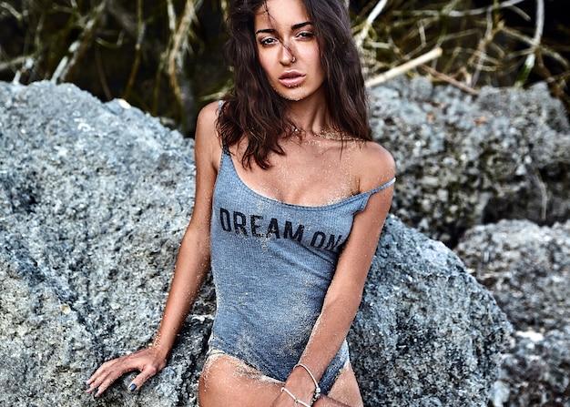 Retrato do modelo bonito caucasiano mulher bronzeada com cabelos longos escuros em traje de banho posando perto de pedras na praia