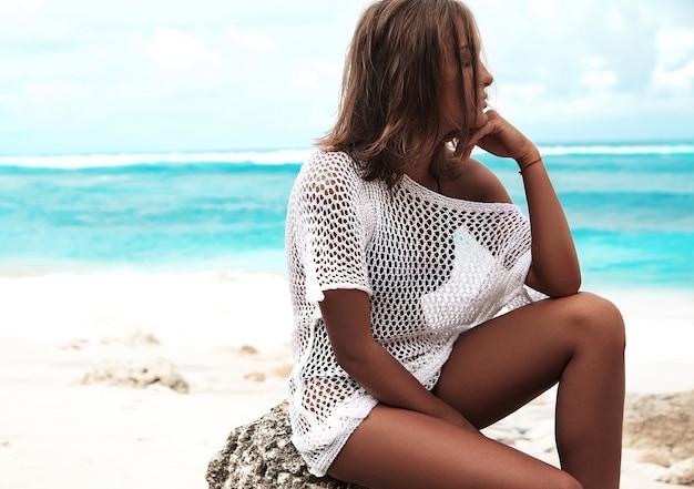 Retrato do modelo bonito caucasiano mulher bronzeada na blusa branca transparente, sentado na praia de verão e fundo azul oceano