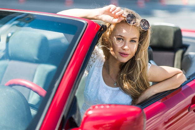 Retrato do modelo bonito da mulher sexy da forma nos óculos de sol que sentam-se no carro convertível luxuoso vermelho com fundo do mar e do céu. jovem que conduz na viagem no dia ensolarado de verão. mar e céu. cabrio vermelho.