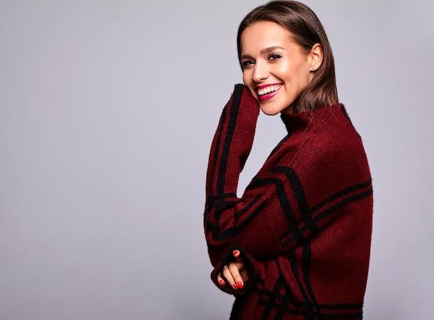 Retrato do modelo bonito feliz mulher morena bonita com roupas de camisola vermelha quente casual isoladas em cinza com maquiagem de noite e lábios coloridos