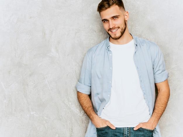 Retrato do modelo bonito jovem sorridente, vestindo roupas de camisa casual. moda elegante homem posando