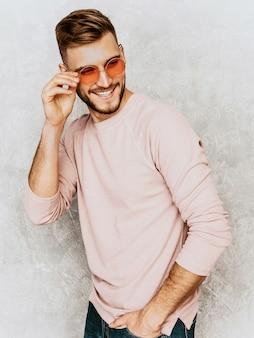 Retrato do modelo bonito jovem sorridente, vestindo roupas de verão casual rosa. moda elegante homem posando em óculos de sol redondos