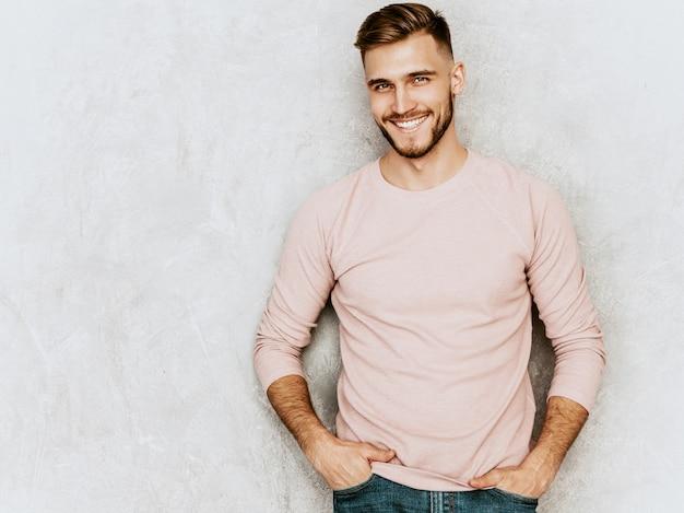 Retrato do modelo bonito jovem sorridente, vestindo roupas de verão casual rosa. moda elegante homem posando