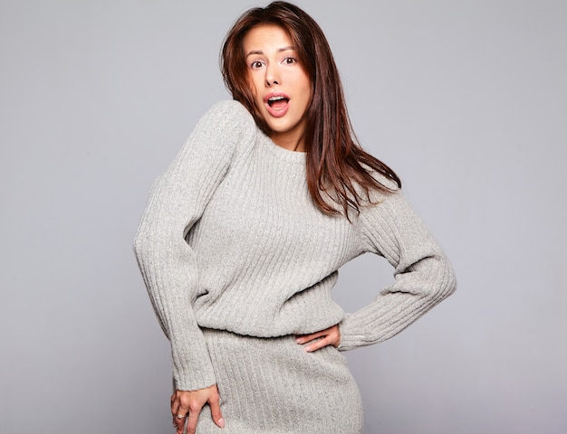 Retrato do modelo bonito mulher morena bonita com roupas de suéter cinza outono casual sem maquiagem isolada em cinza