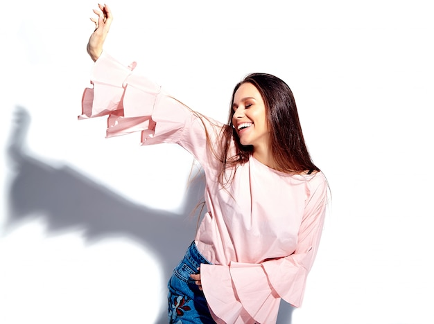 Retrato do modelo caucasiano sorridente mulher morena bonita blusa rosa brilhante e verão azul elegante jeans com flores imprimir