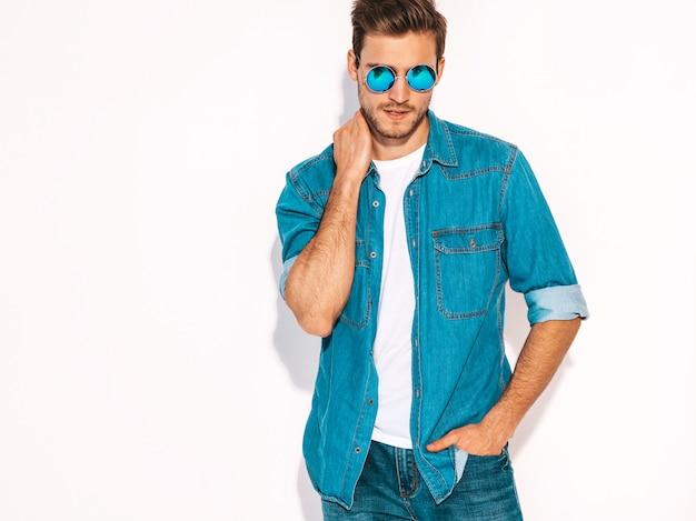 Retrato do modelo de elegante jovem sorridente bonito vestido com roupas jeans e óculos de sol. homem moda