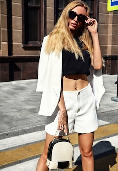 Retrato do modelo de empresária moderna moda sexy em terno branco, posando no fundo da rua com bolsa