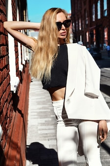 Retrato do modelo de empresária moderna moda sexy em terno branco, posando no fundo da rua por trás do céu azul