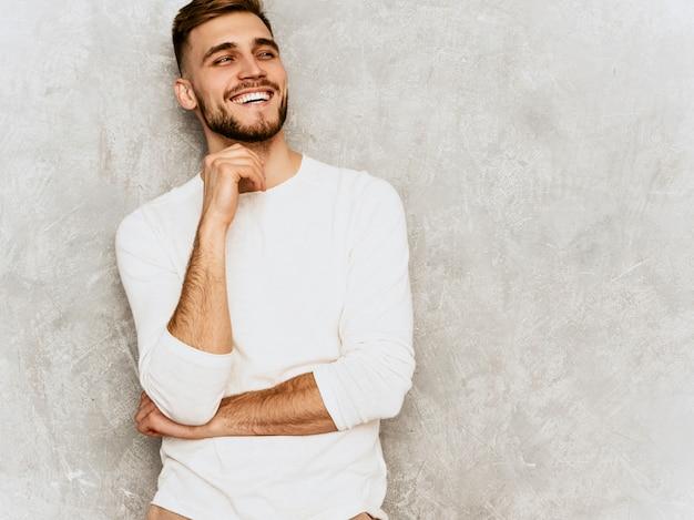 Retrato do modelo de empresário de hipster sorridente bonito vestindo roupas de verão casual branco ... tocando o queixo