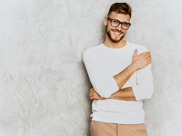 Retrato do modelo de empresário de hipster sorridente bonito vestindo roupas de verão casual branco.