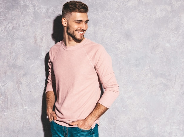 Retrato do modelo de empresário de hipster sorridente bonito vestindo roupas de verão casual rosa.