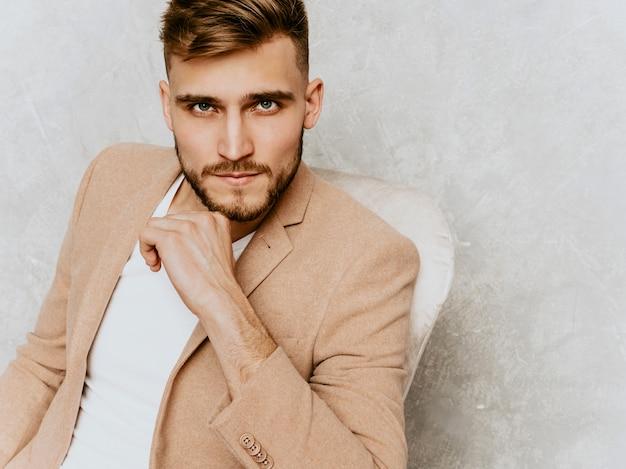 Retrato do modelo de empresário de hipster sorridente bonito vestindo terno bege casual. sentado na cadeira no interior